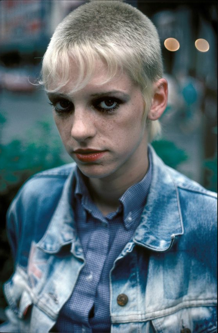 girl with mullet, blonde very short hair with longish bangs, black eye make up and red lipstick, wearing stone washed denim jacket and blue shirt