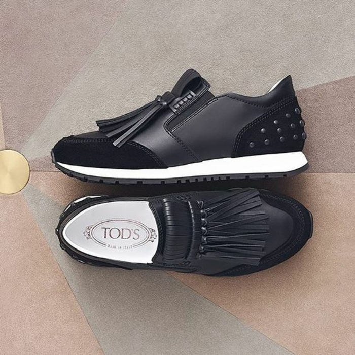 close up of black leather shoes, with black studs and tassels, white and black rubber soles
