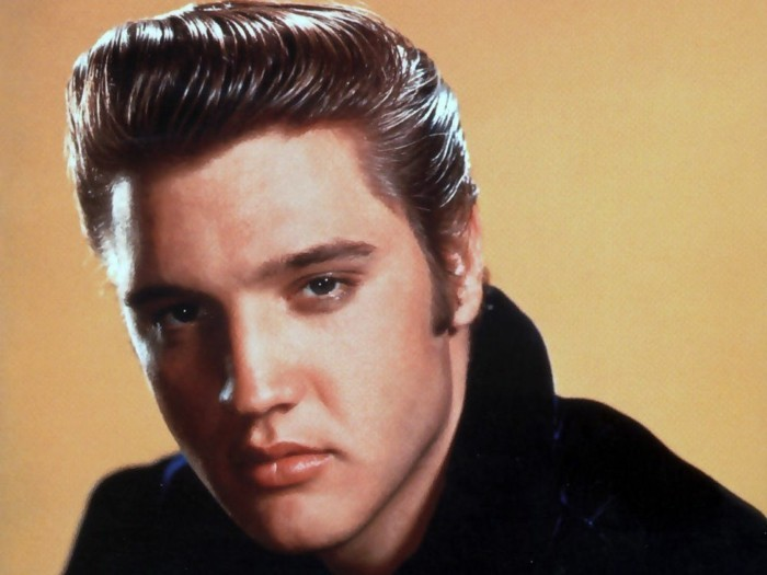 color photo of elvis presley, gelled up shiny dark hair, black top and yellow background, close up with shadows on face
