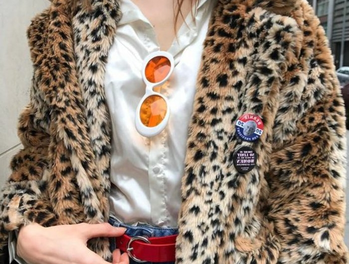 close up of a woman's torso, wearing white silky shirt and faux fur coat with animal print, pins and white sunglasses with orange frames, hand on red belt