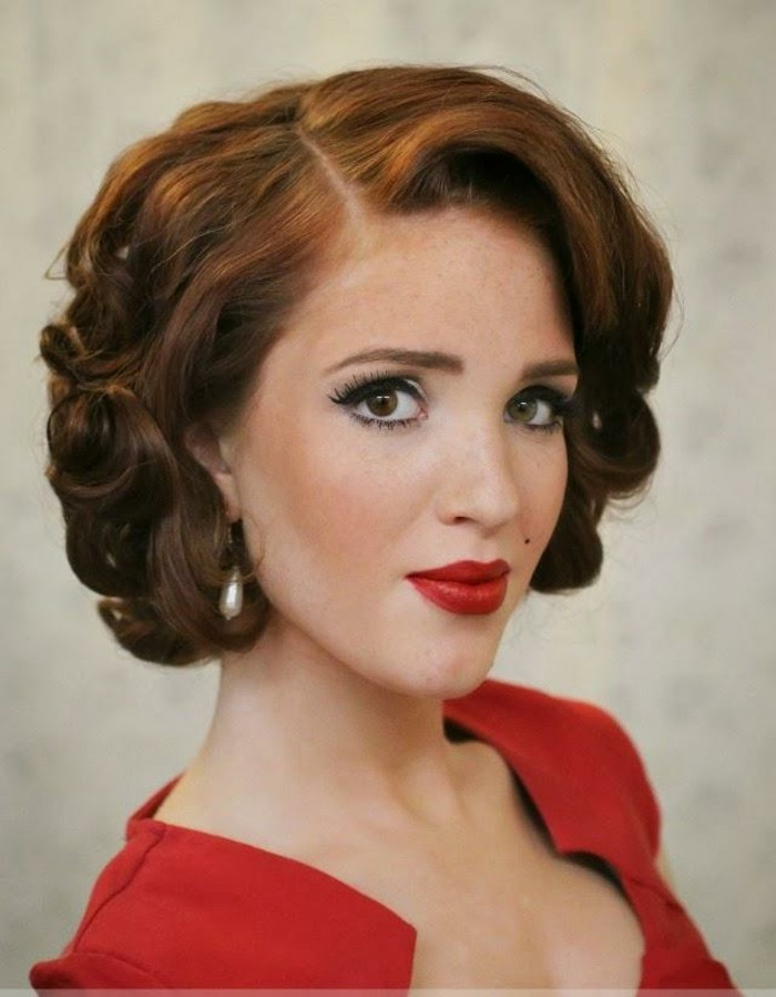 ginger-haired woman with 1940's styled short hair with curls, red lipstick and top, beauty spot fake lashes and mascara in close up