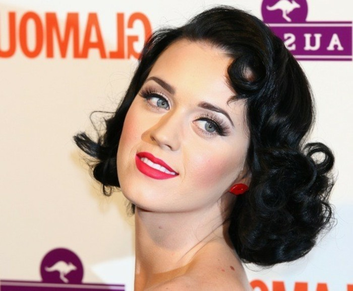 close up of katy perry, short curly retro styled hair, big fake lashes mascara and bold black eyeliner, vibrant red lipstick, blue eyes lip-shaped stud earrings