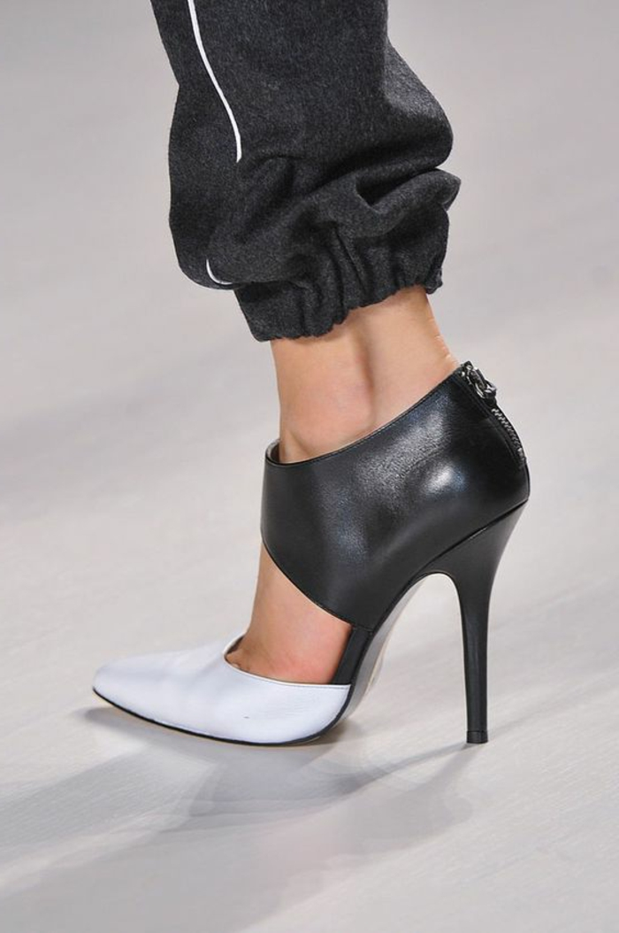 close up of a leg wearing dark grey sweatpants, ankle-high high-heeled shoes in black and white