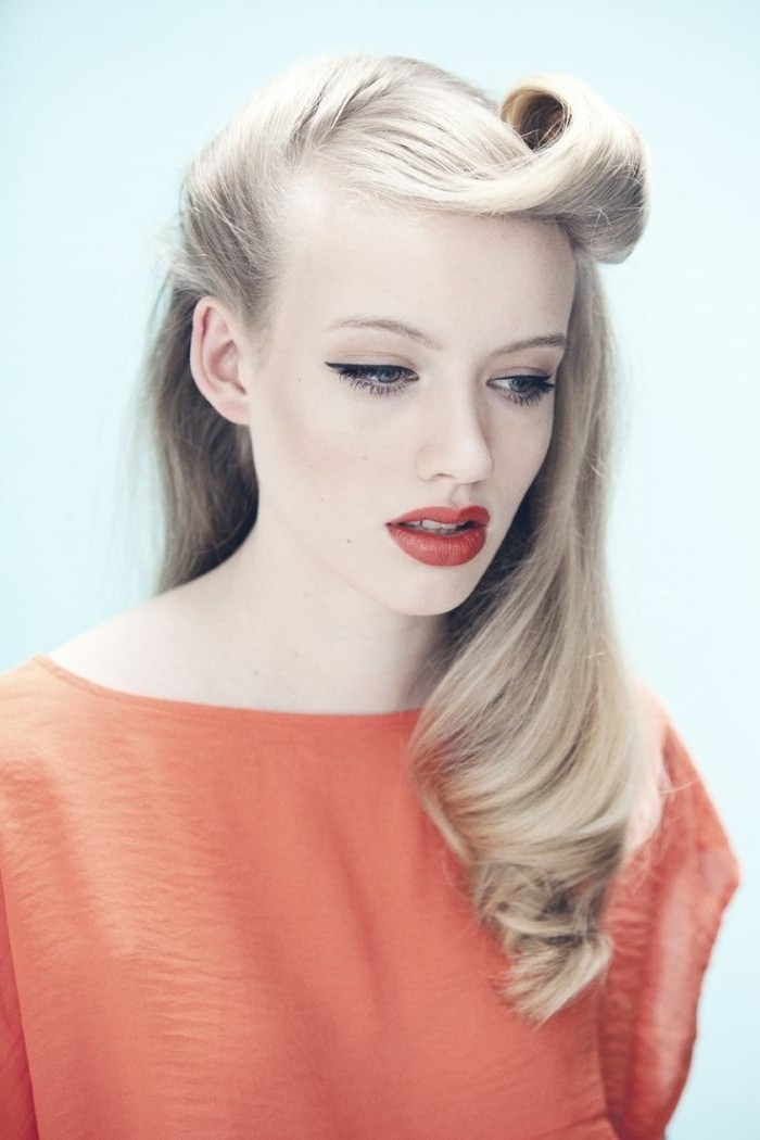 pinup hair, pale woman with light blonde hair, one victory roll and slight curl, red lipstick and eyeliner, wearing pale coral red top