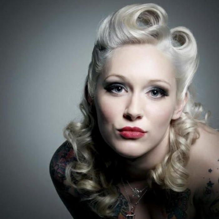 rockabilly hairstyles, pale woman with platinum retro hair, dramatic eye make up and red lipstick, close up with shadows on body and face