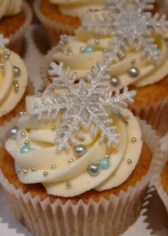 christmas flavors, close up of batch of vanilla cupcakes, pale yellow frosting, decorated with silver sparkly snowflake shape, pale blue and silver pearls