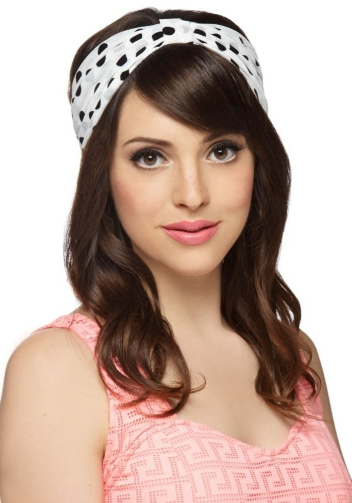 young woman with retro brown hair, side bangs and white bandanna with black polka dots, wearing pale coral pink top and lipstick