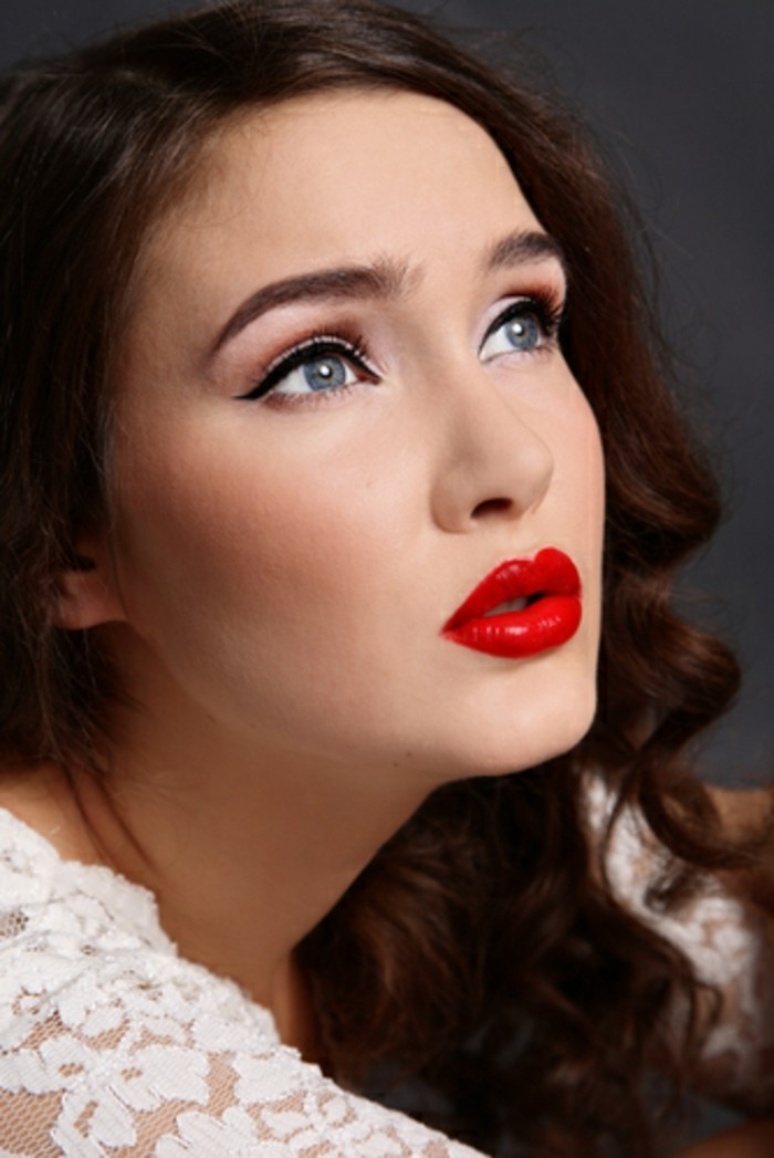 brunette woman with bold red lipstick, black eyeliner and fake lashes, curly hair and blue eyes, white lacy top