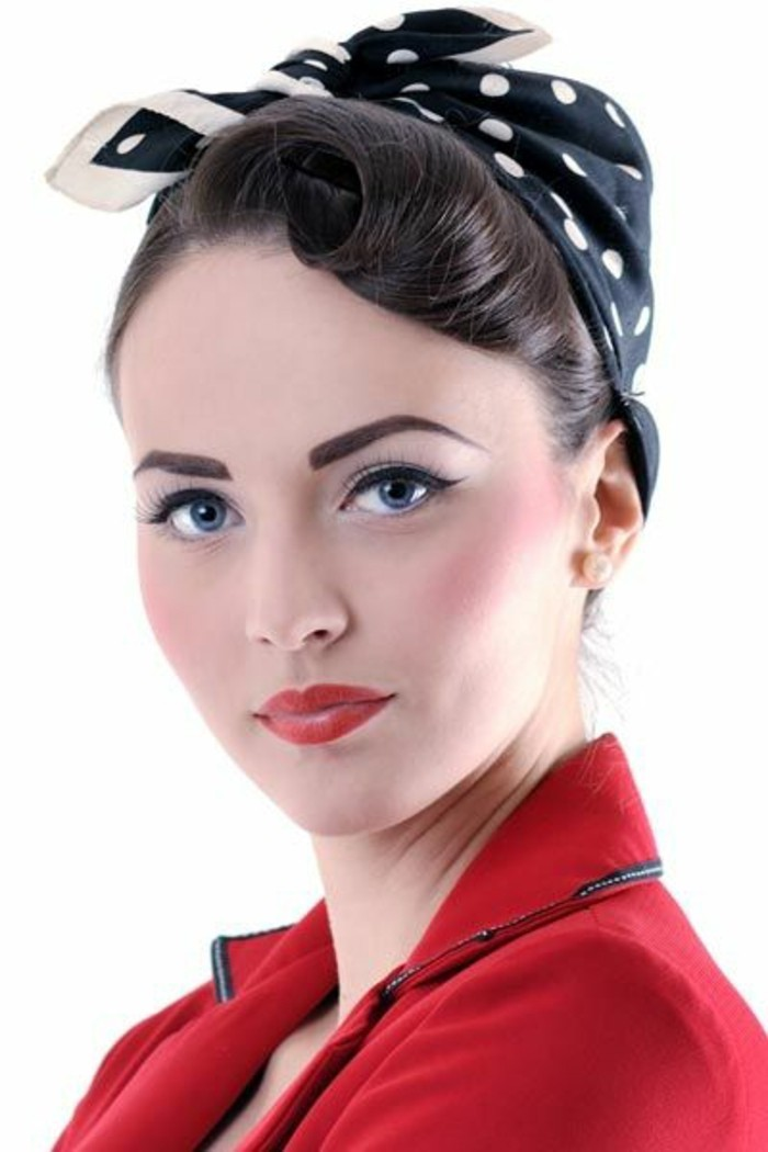 dark-haired woman wearing black bandanna with white polka dots, eyeliner mascara and blush, penciled eyebrows and red lipstick, red blazer with black details