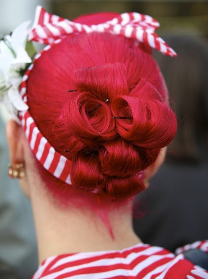 back view of red hair tied up in a hair bun made of curls, striped red and white hair band with bow, big white flower and earrings, striped red and white top