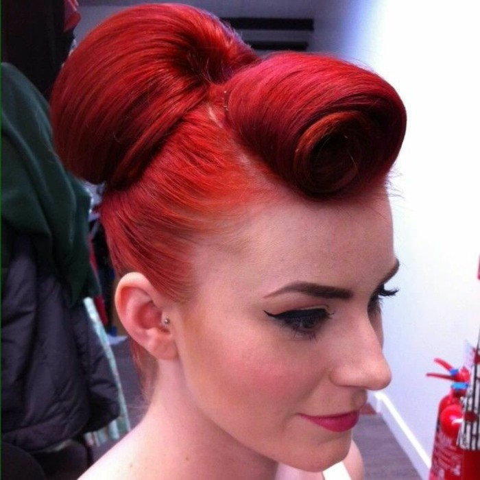 red-haired woman, with unusual curled bangs and a hair bun, wearing black eyeliner and fake lashes, dyed eyebrows and lipstick