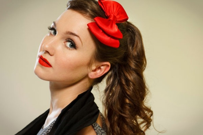 pin up hairstyles, close up of woman with retro side ponytail, two bright red bows and red lipstick, blue eyes fake eyelashes and a black scarf