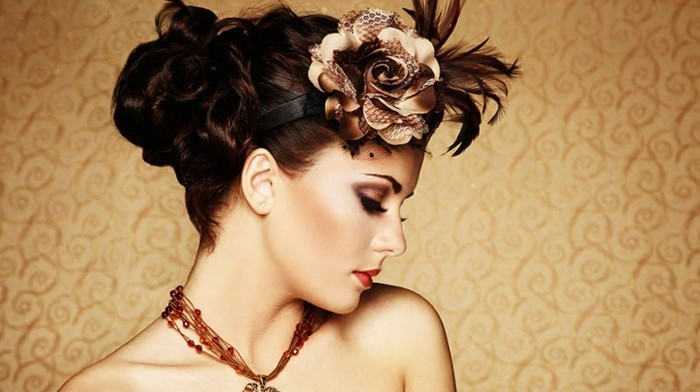 woman with retro updo, brunette hair with brown fake rose ornament and dark feathers, close up in profile, nude shoulders and an amber necklace, heavy eye make up