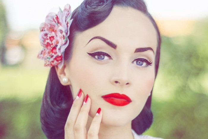 vintage hairstyles, young woman with retro 1950's hairstyle and colorful fake flower hair ornament, pearl earring and heavy make up