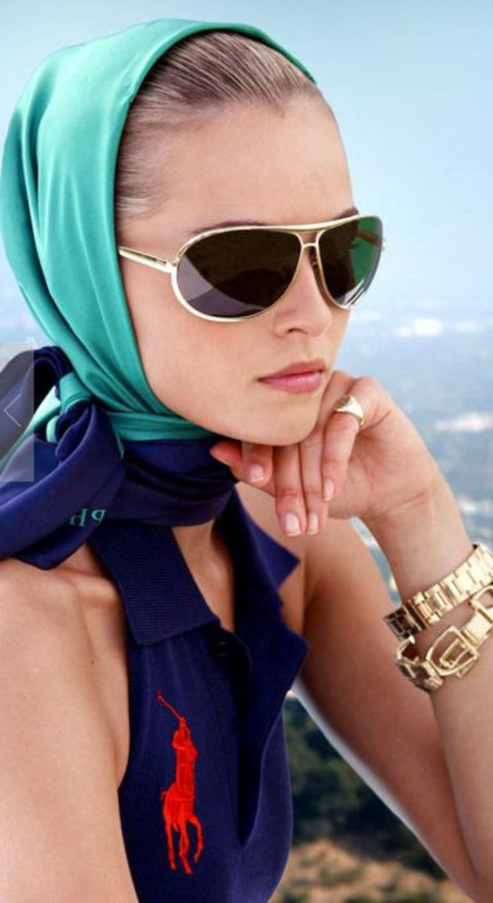 close up of woman with turquoise headscarf, wearing sunglasses and a blue sleeveless shirt with red big polo logo, golden wristwatch bracelet and ring