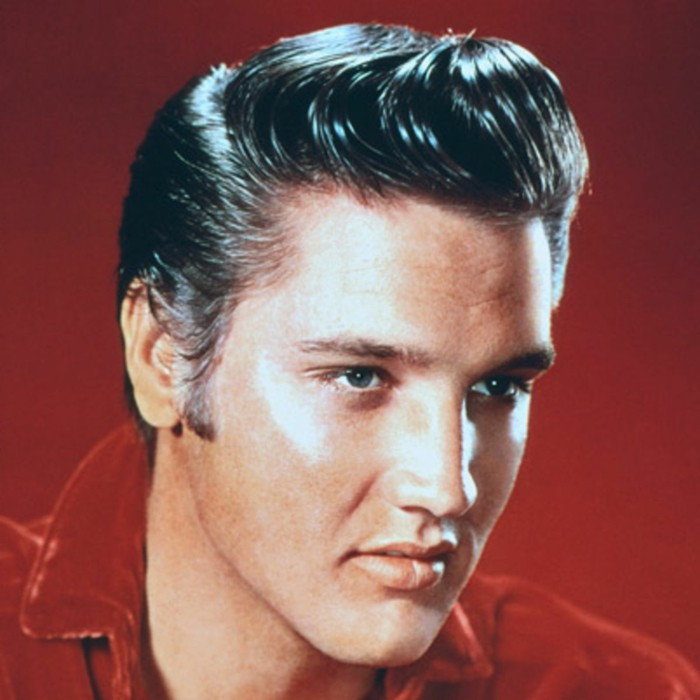 close up of older elvis presley, black gelled up hair, red shirt and background and blue eyes, colorized vintage photo