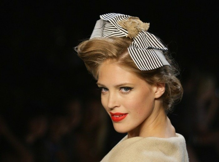 blonde woman close up, retro hairstyle with big striped hair bow, bright red lipstick and black mascara, camel-colored top and black background