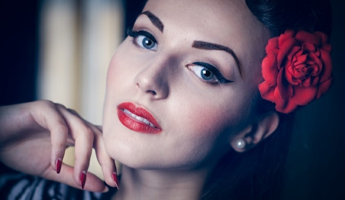 vintage hairstyles, close up of woman with heavy 1950's inspired make up, penciled eyebrows and fake red rose behind ear