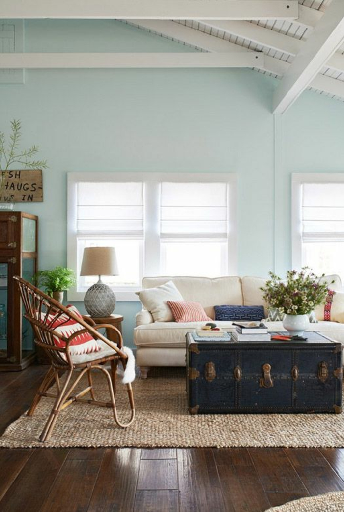 color schemes for living rooms, dark wooden floors, cream chunky carpet, massive old wooden chest used as table, light cream sofa and wooden chair with cushion, light blue walls and white ceiling with wooden beams