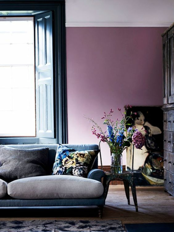 interior painting, purple wall, grey and black sofa with colorful cushion, black open door and brown cupboard, dark wooden chair, small dark table with clear jar containing flowers