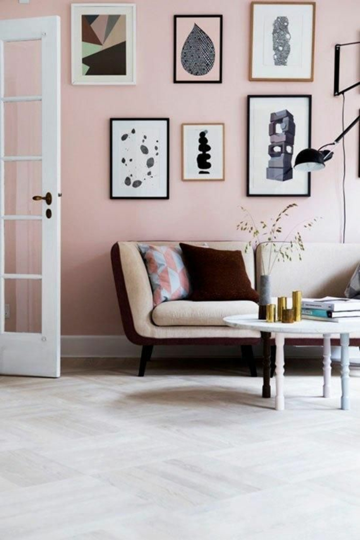 pink wall with six framed images, pale cream and brown sofa with two cushions, pale grey floor and open white door with glass inserts, small table with pastel colored legs
