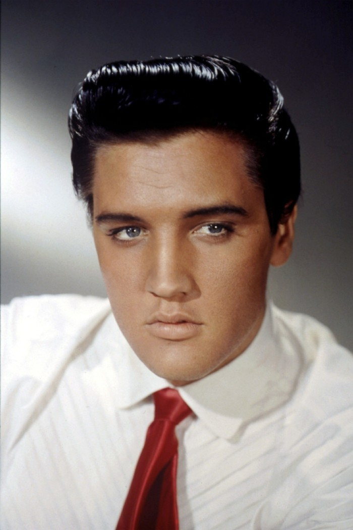 older elvis presley in colorized photo, shiny black gelled up hair, white shirt and shiny red tie, blue eyes and grey background