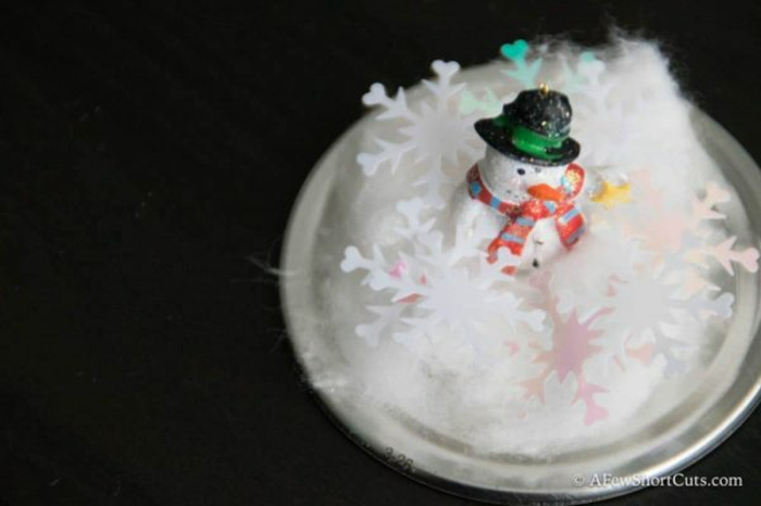 diy christmas gifts, jar lid with cotton, white and pink snow-shaped confetti, a small snowman figurine with hat and scarf, black background