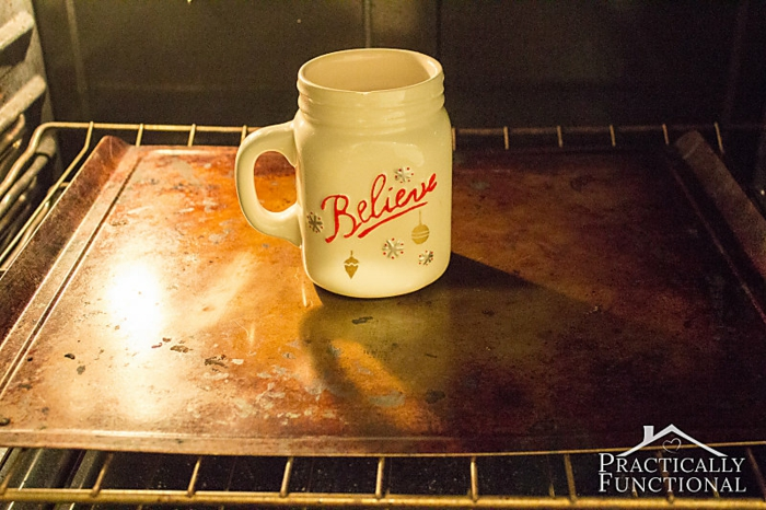 diy christmas crafts, white ceramic mug with red writing, and blue and gold hand-painted details, on baking tray inside an oven