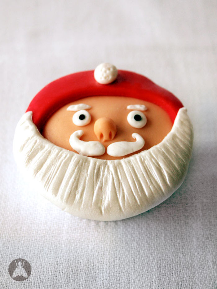close up of cupcake with orange, red black and white fondant icing, in the shape of santa's head