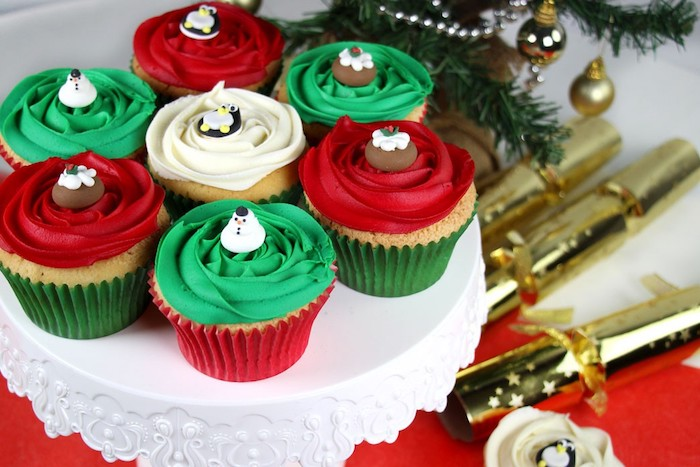 seven cupcakes on white dish, three with red frosting, three with green frosting, one with white frosting, decorated with festive fondant shapes