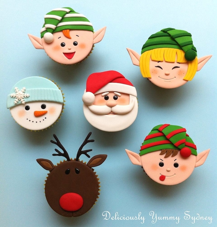 christmas flavors, six cupcakes decorated with colorful fondant icing, made to look like santa, snowman, rudolph and three elves, on pale blue background