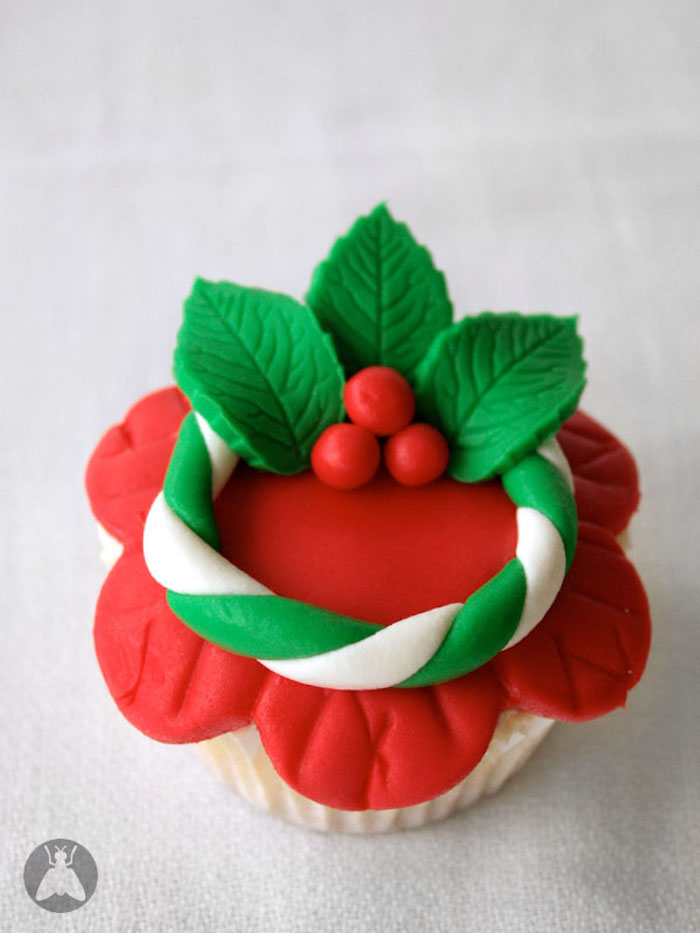cupcake with red fondant icing shaped like flower, decorated with white and green fondant wreath with holly