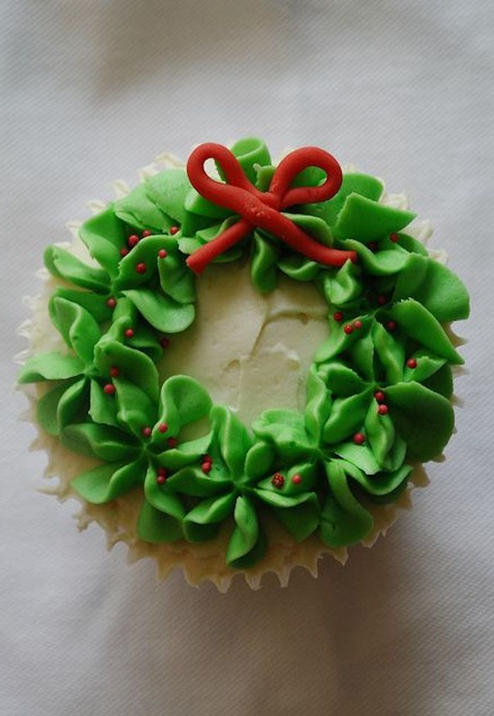 close up of cupcake with white icing, made to look like an x-mas wreath with green frosting, with small fondant bow and red sprinkles