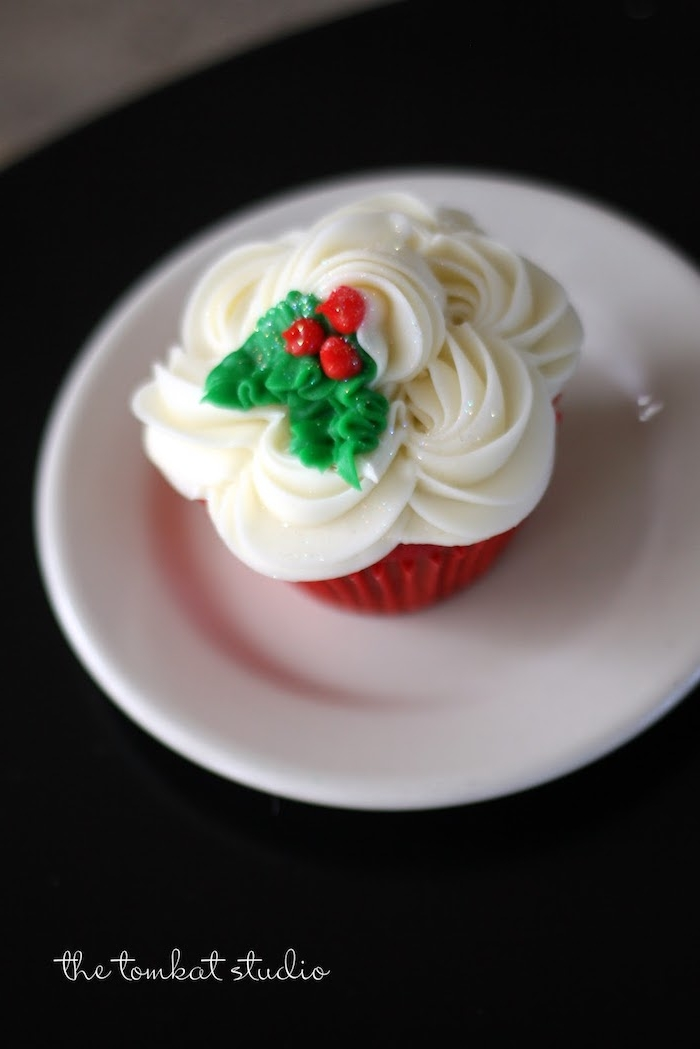 red cupcake in red wrapper, with white frosting, decorated with fondant holly, white plate on black background