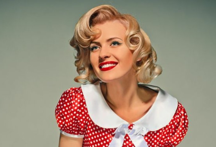 pinup hair, smiling woman with white teeth and red lipstick, wearing red retro dress with white polka dots, white collar and bow and puffy short sleeves, short blonde hair with retro curls