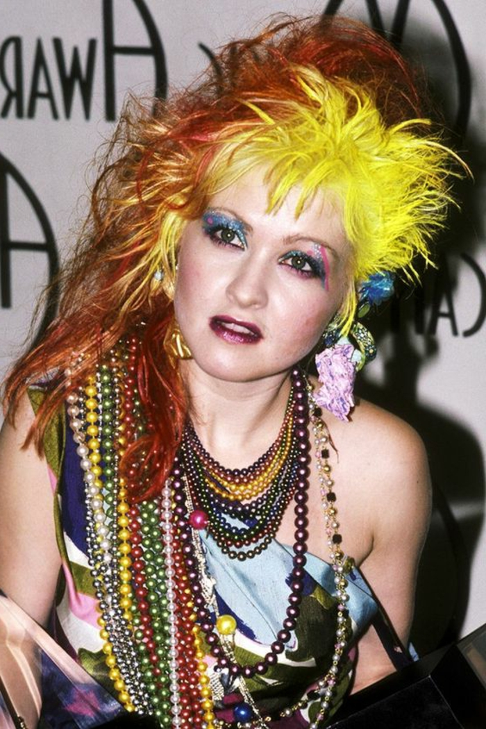 cyndi lauper with a messy punk hairstyle is neon yellow and orange, blue and pink glittering eye shadow, lots of necklaces with colorful beads, dark pink lipstick and shiny top
