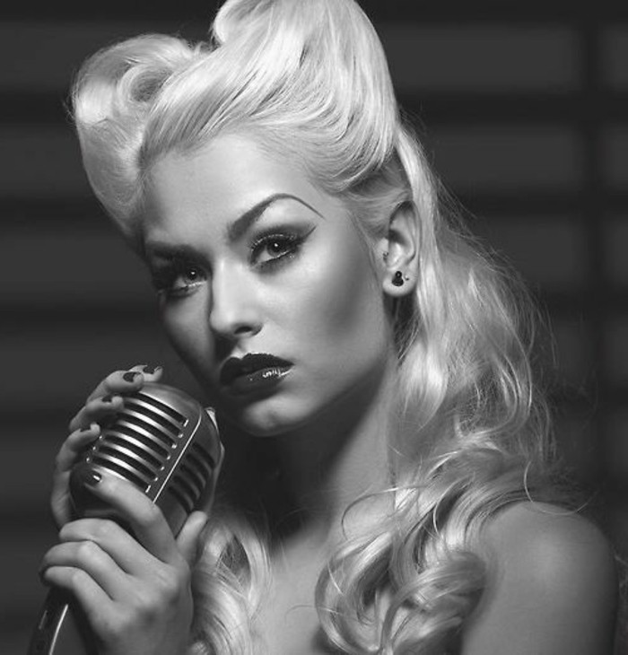 pinup hair, woman with light blonde hair and victory rolls, arched eyebrows heavy make up and dark shiny lipstick, holding a retro microphone