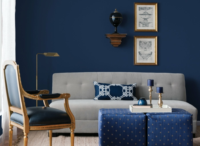 living room color ideas, dark blue wall and light grey sofa, navy blue chair with gold details, two blue ottomans with yellow stars, gold lamp and two framed pictures