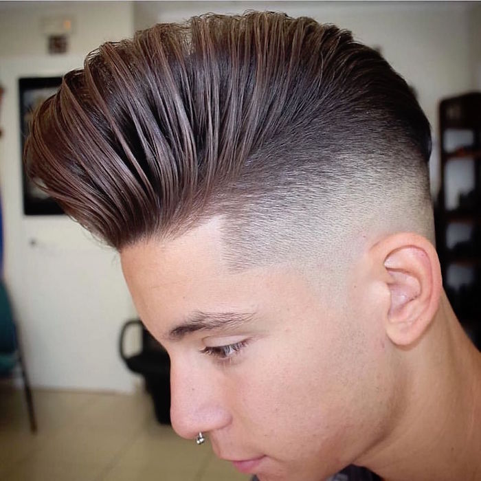 disconnected haircut, boy with nose ring, facing down and sideways, shortly trimmed hair on side, long and styled up on top, comb-over or pompadour style