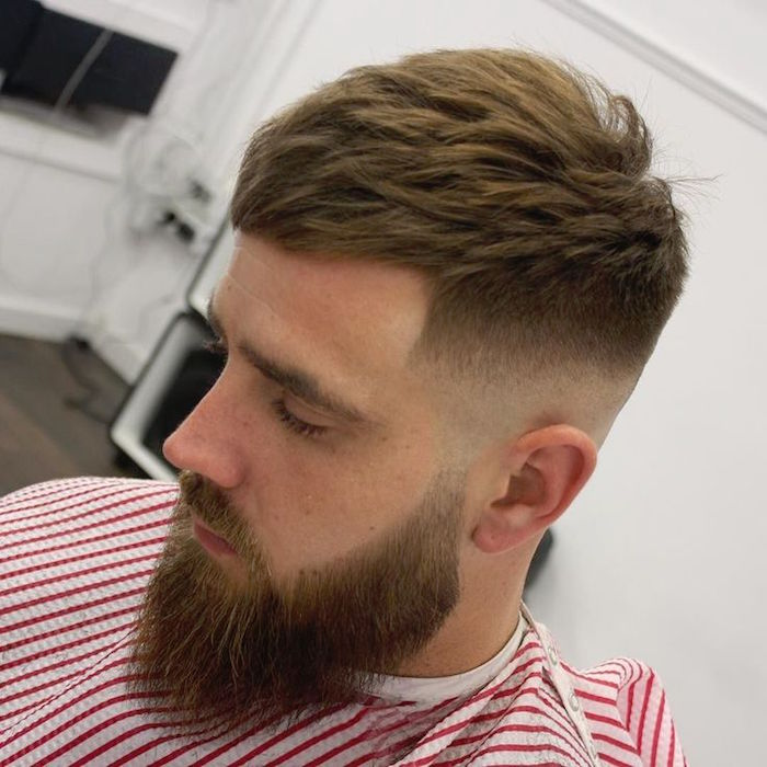 faded undercut, man with beard an mustache, facing down and to the side, hair shaven on the sides but gradually getting longer on top, red and white striped barber's robe