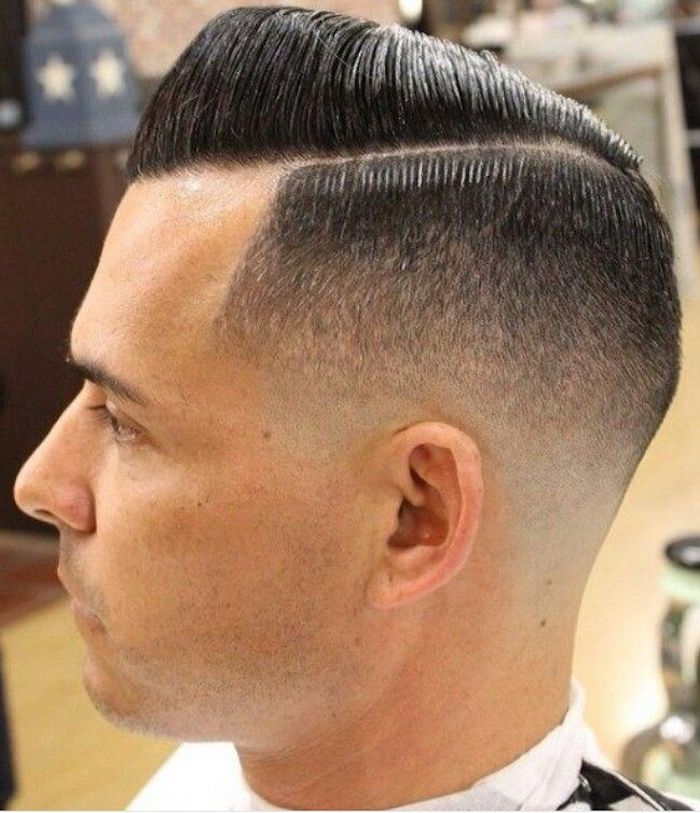 side part undercut, man with dark hair parted on one side, longer on top and combed over with gel, shorted on the sides