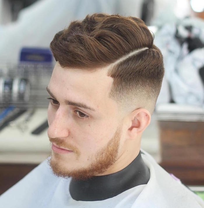 how to style a undercut, young man with auburn hair, cut short on side and longer and wavy on top, seen in close up from above, with red beard and mustache, dark eyes and black and white barber's robe