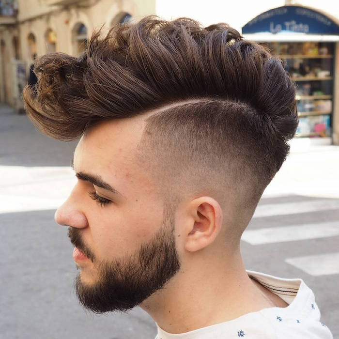 side part undercut, young bearded and mustached man in profile, white top with blue details, dark hair shaven on the side and long on top, gelled up and messy