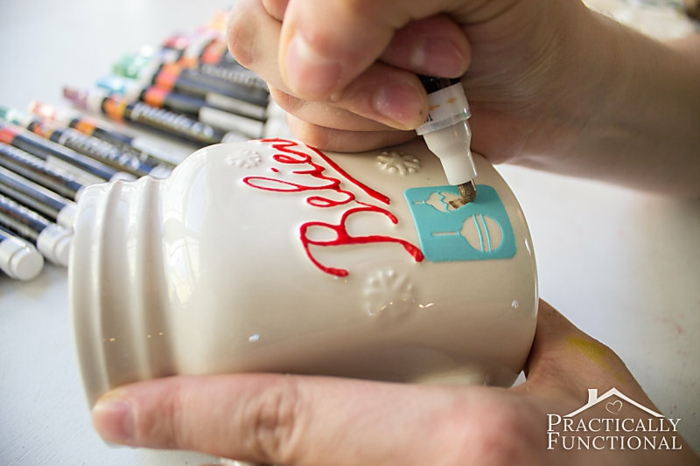 diy christmas crafts, blue stencil sticker stuck to white ceramic mug, hand painting over it with gold colored marker, hand holding mug and markers in background
