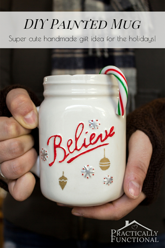 diy christmas crafts, two hands holding a big white mug with handle, with the word believe written in red, hand-drawn snowflakes and Christmas ornaments in blue and gold, a peppermint cane inside