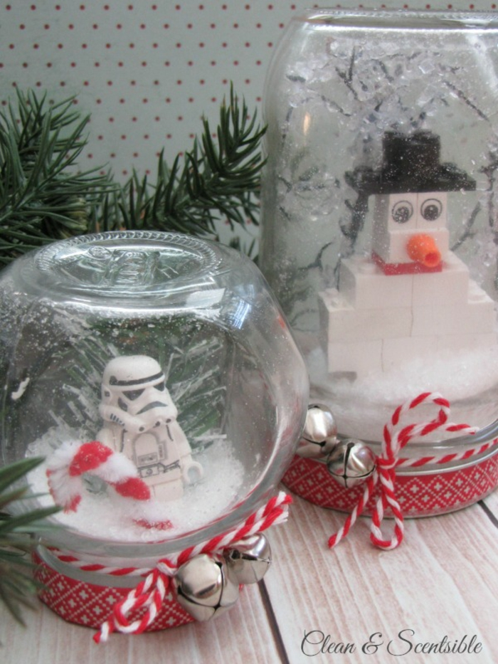 two snow globes made from a small and a large jar, with fake snow and lego figurines, a snowman made of lego, a lego star wars storm trooper, tied with red and white string with two bells each, pine branches in background
