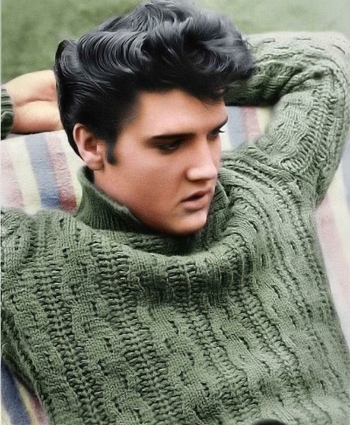 colorized photo of elvis presley, leaning on striped surface, with arms behind head, shiny black wavy gelled up hair, chunky green cable knit turtle neck sweater