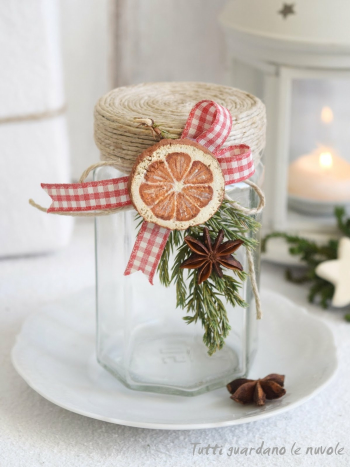 christmas crafts for adults, an empty clear jar decorated with string, red and white checkered ribbon, a wooden ornament painted like an orange slice, star anise and a green twig, placed on a white plate