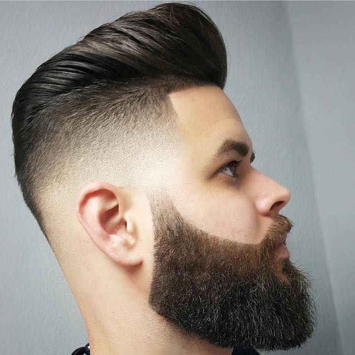 slicked back undercut, pale man with dark hair, facing sideways and in close up, trimmed beard and mustache, very short side hair and puffy pompadour style top hair, brushed back with gel
