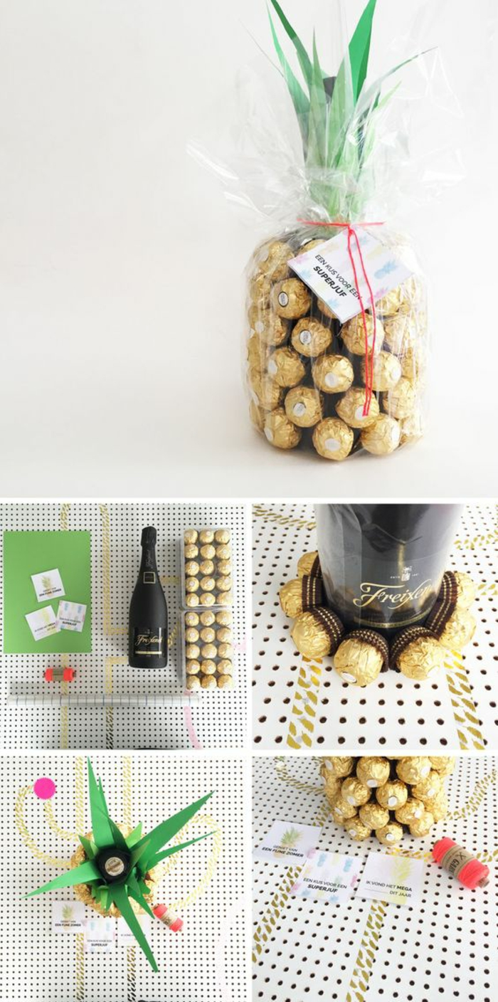 pineapple made of chocolates in golden wrappers, a black champagne bottle, some green and white paper, red thread and a ruler